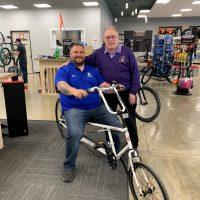 Photo of Fred Honerkamp standing beside Adam Morton as he sits on his new recumbent bike