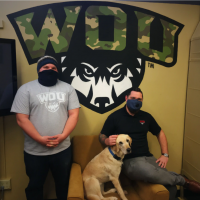 Two student veterans posing with a dog