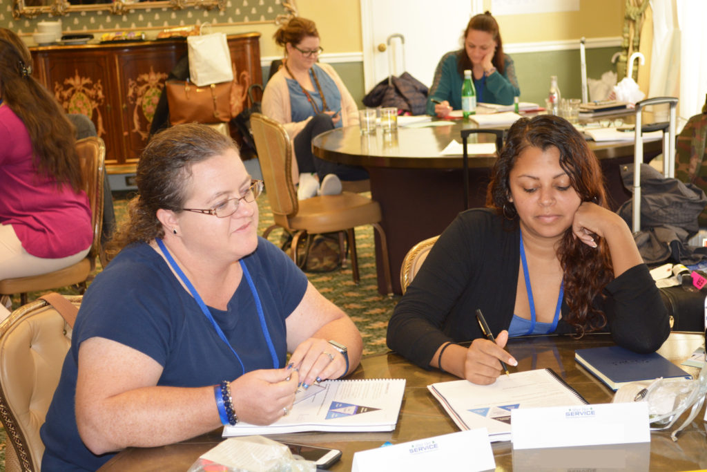 2 After Her Service participants focusing on an activity