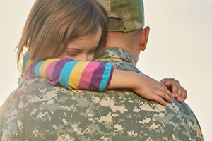Little female child is hugging a soldier. Close up portrait of happy girl is hugging her father in military uniform.