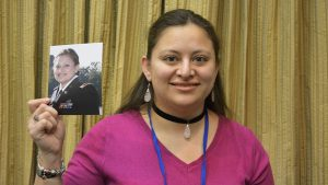 Clarizza Paz, and After Her Service participant, holds a photo of herself from when she was in an Army uniform
