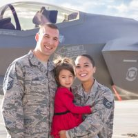 Alex Sawin in her Air Force uniform standing beside her husband and holding her young daughter