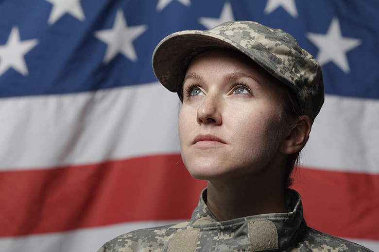 Photo of a female soldier in uniform standing in front of an American flag and looking into the distance