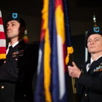 Two individuals in military uniforms holding the American flag