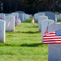 Image of a military cemetery with American flags