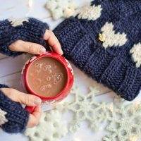 Picture showing a person's hands wearing mittens and holding a mug of hot chocolate